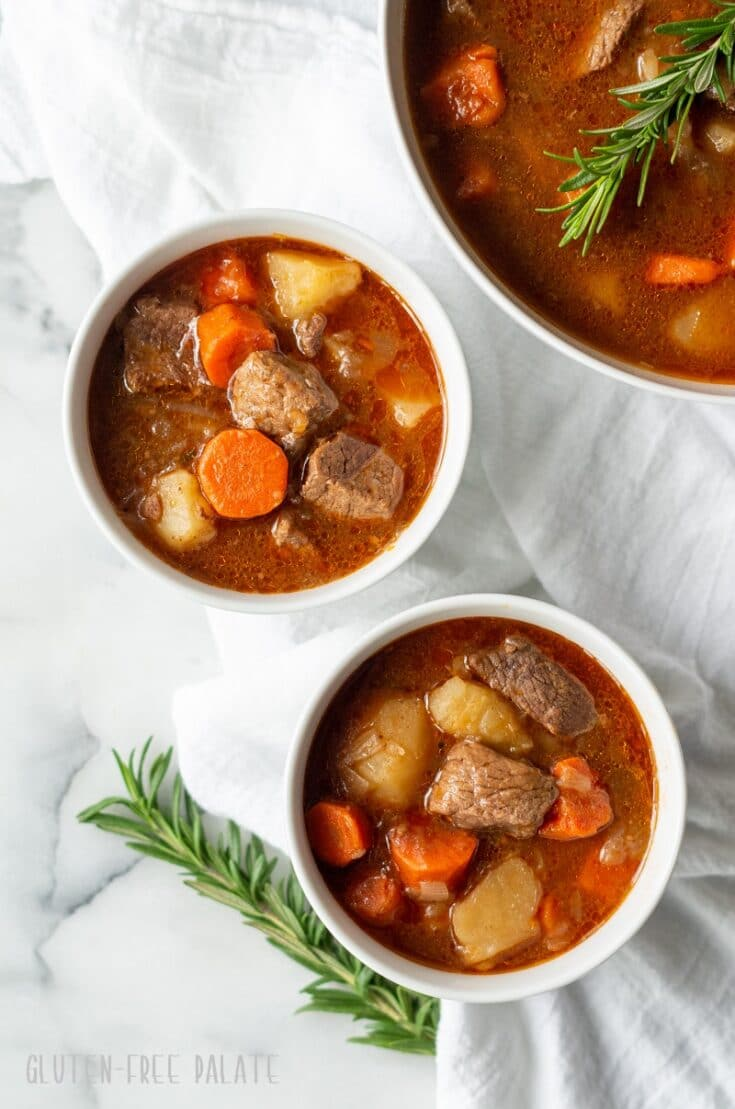 two bowls of gluten free beef stew nex to a pot of beef stew with springs of rosemary next to it