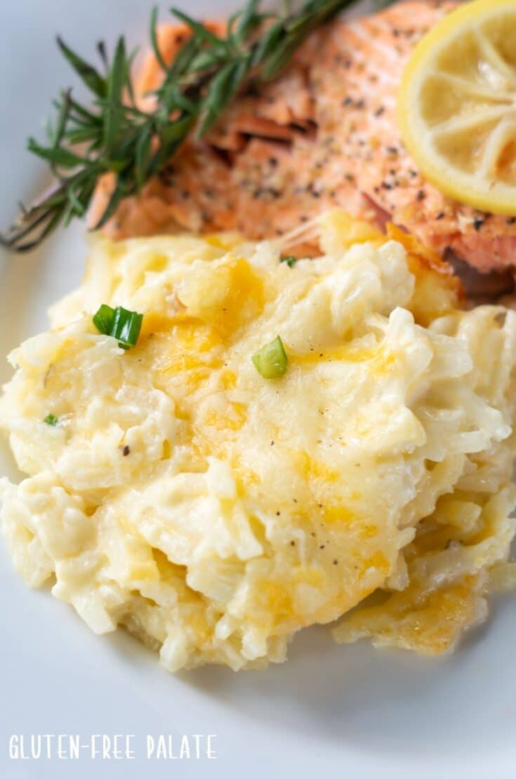 Cheesy Potatoes on a plate with salmon and lemon and a sprink of rosemary
