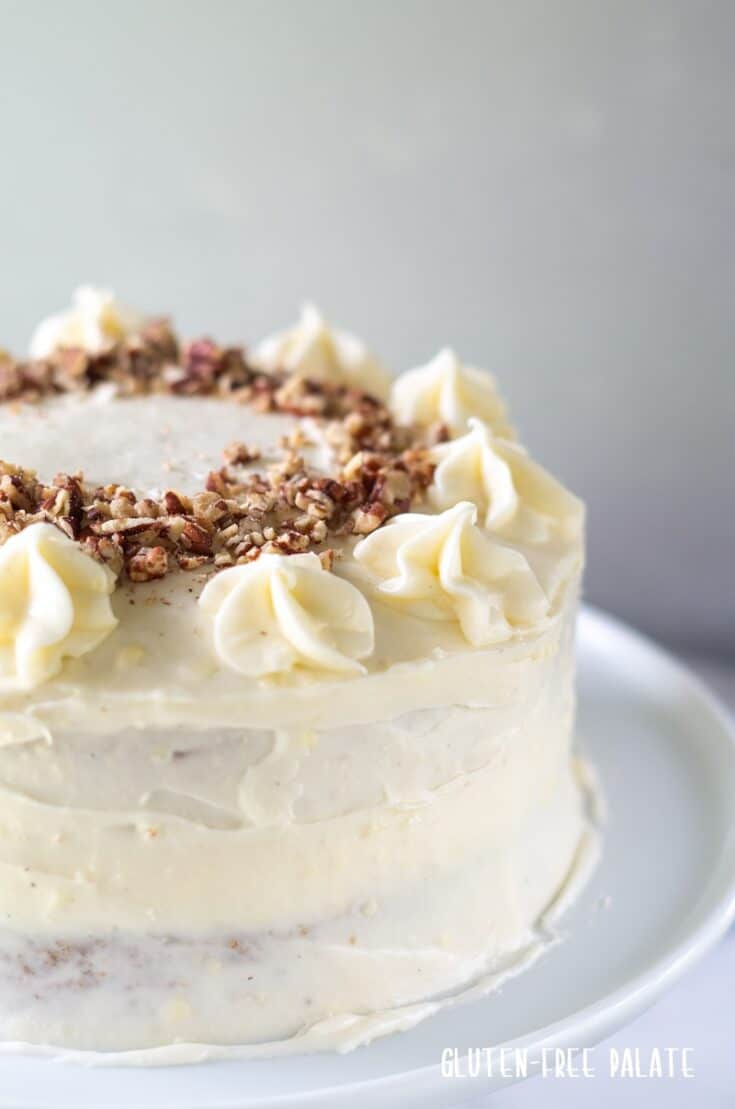 side view of a whole gluten free carrot cake topped with chopped nuts on a wihte cake stand