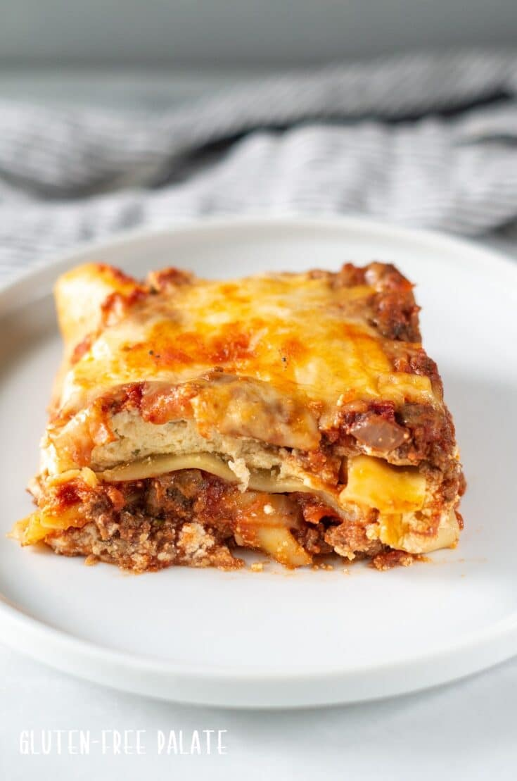 a serving of gluten free lasagna on a white plate