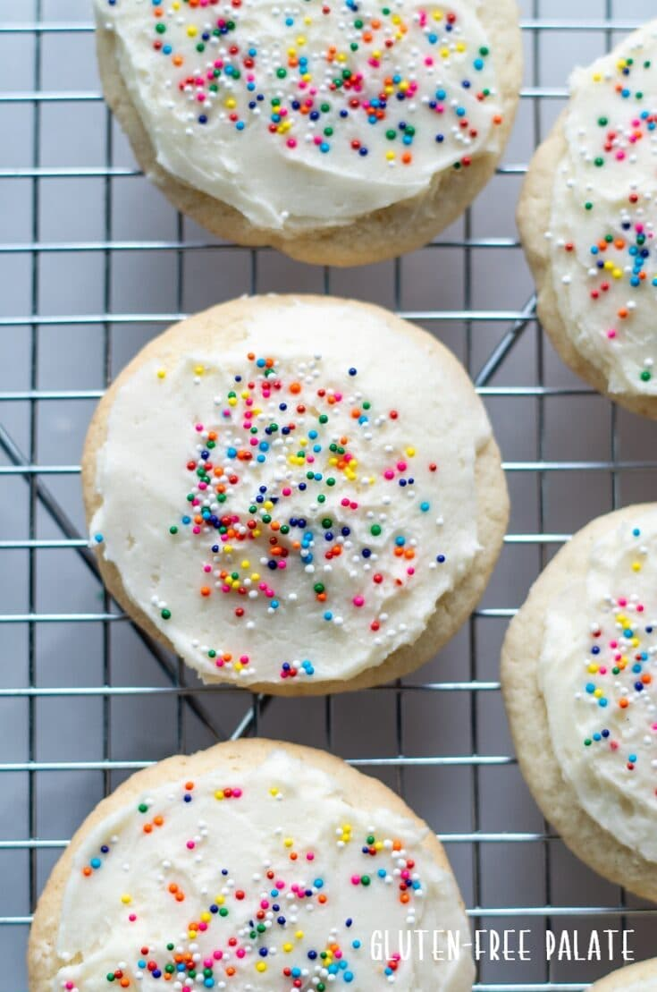 Gluten Free Sugar Cookies with white frosting and colored sprinkles on a cooling rack