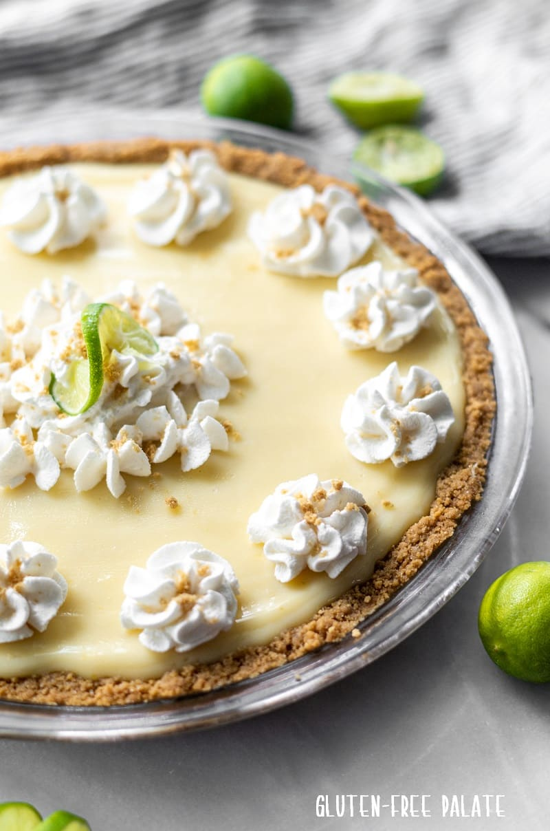 a gluten free key lime pie in a glass pie dish with whipped cream