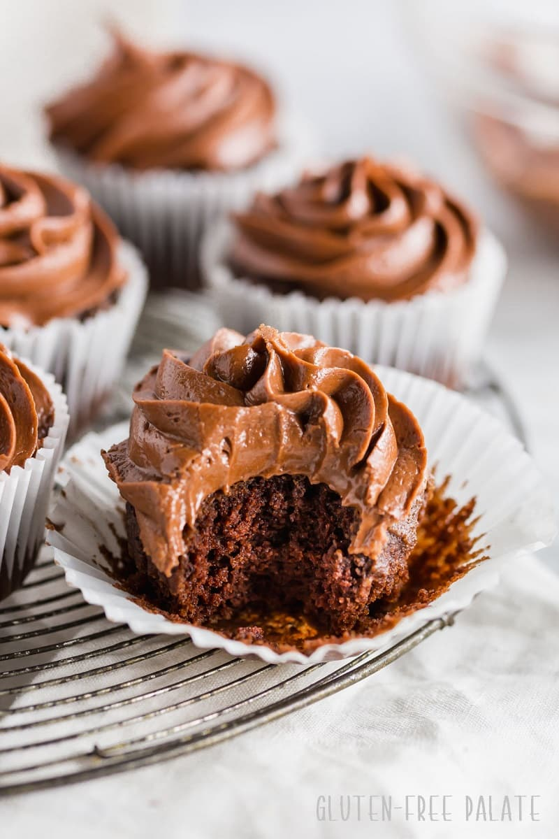 a paleo chocolate cupcake with chocolate frosting, with a bite taken out