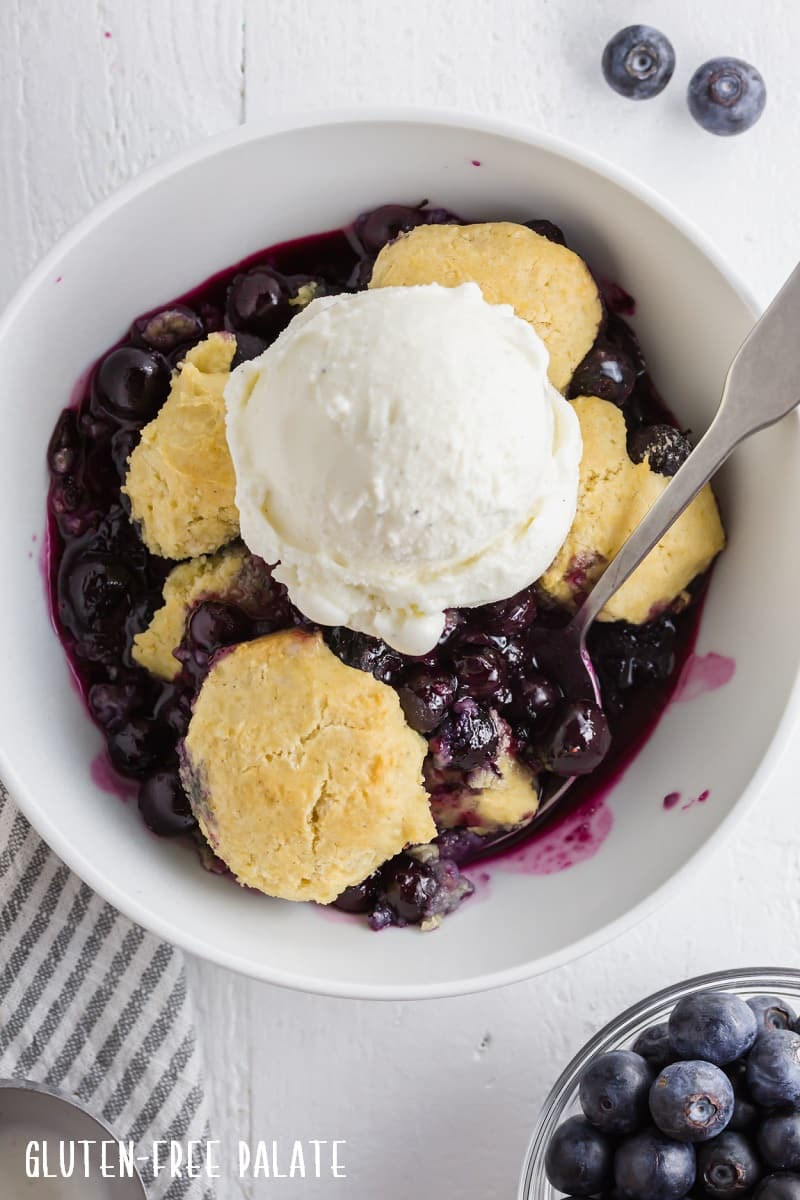 a close up of gluten free blueberry cobbler topped with a scoop of vanilla ice cream