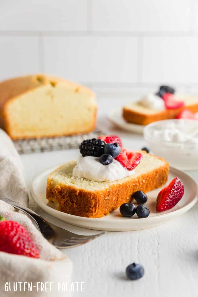 a slice of gluten free pound cake topped with whipped cream and berries