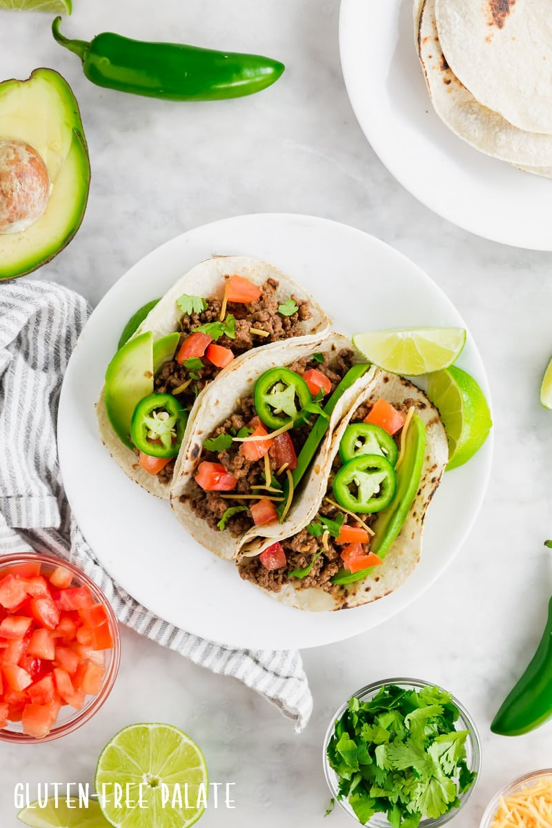 top down view of three gluten free tacos on a white plate