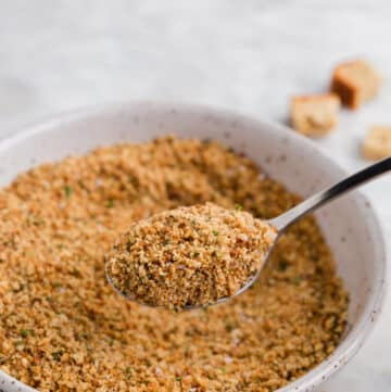 a spoonful of gluten free breadcrumbs over a bowl of bread crumbs