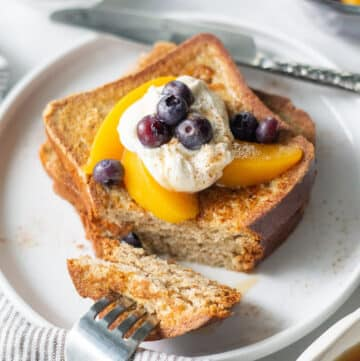 2 slices of gluten free french toast topped with peaches, blueberries, and whipped cream