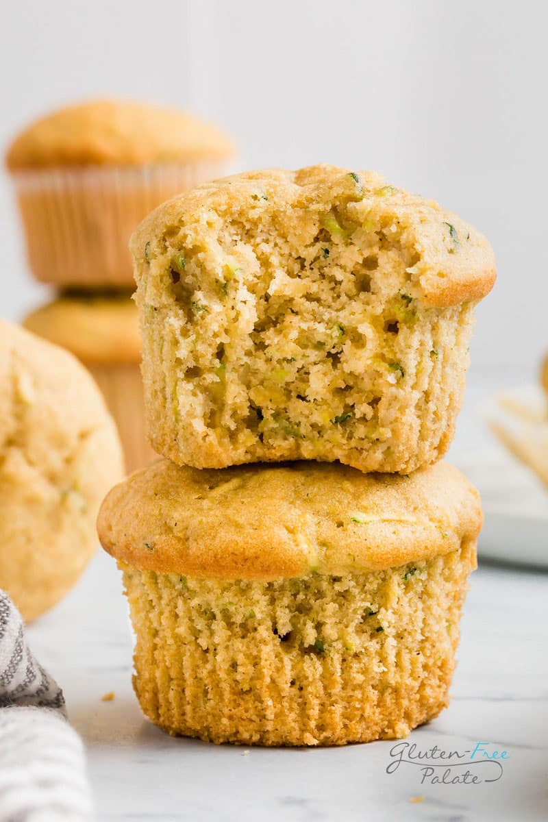 a gluten free zucchini muffin with a bite out on top of another muffin