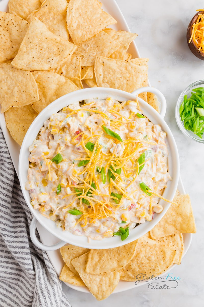 crack corn dip in a white bowl next to tortilla chips