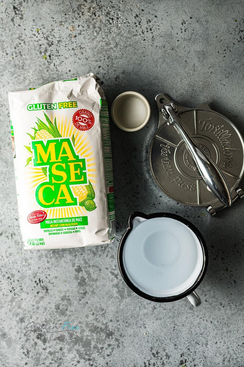 masa flour, water and salt next to a tortilla press