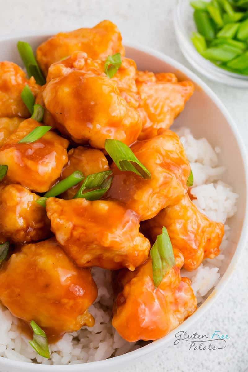 a close up of gluten free orange chicken over rice in a white bowl