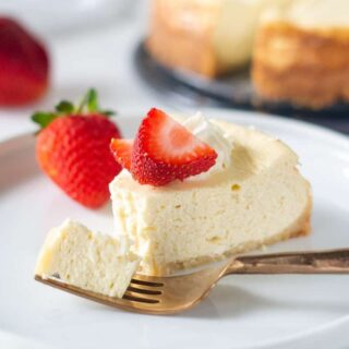 a slice of gluten free cheesecake on a white plate with a bite out and a fork