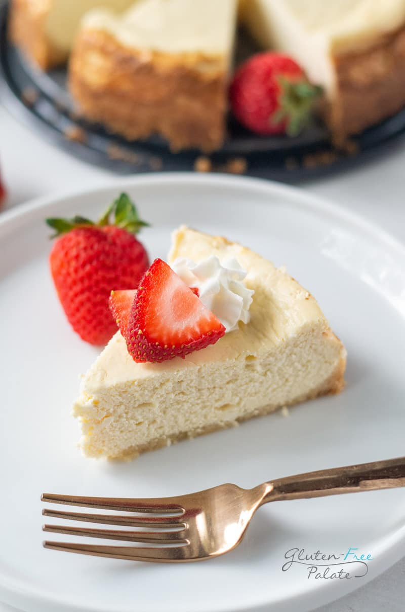 a slice of gluten free cheesecake on a white plate with strawberries on top