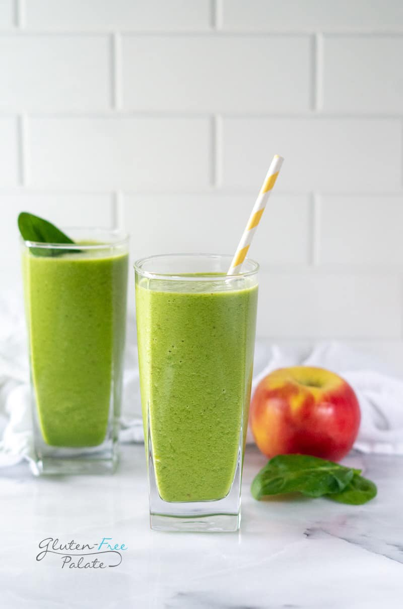 apple spinach smoothie in a glass with a straw