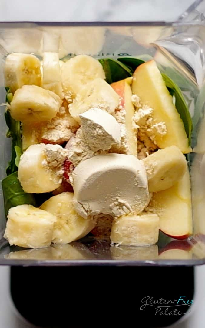 close up of ingredients in a apple spinach smoothie in a blender jar
