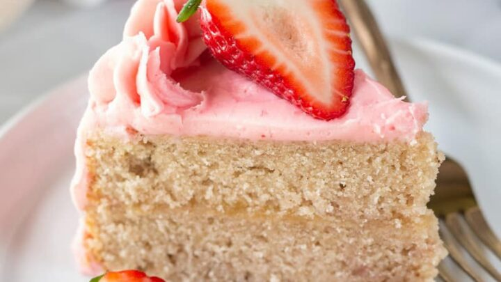 a slice of gluten free strawberry cake topped with sliced strawberries