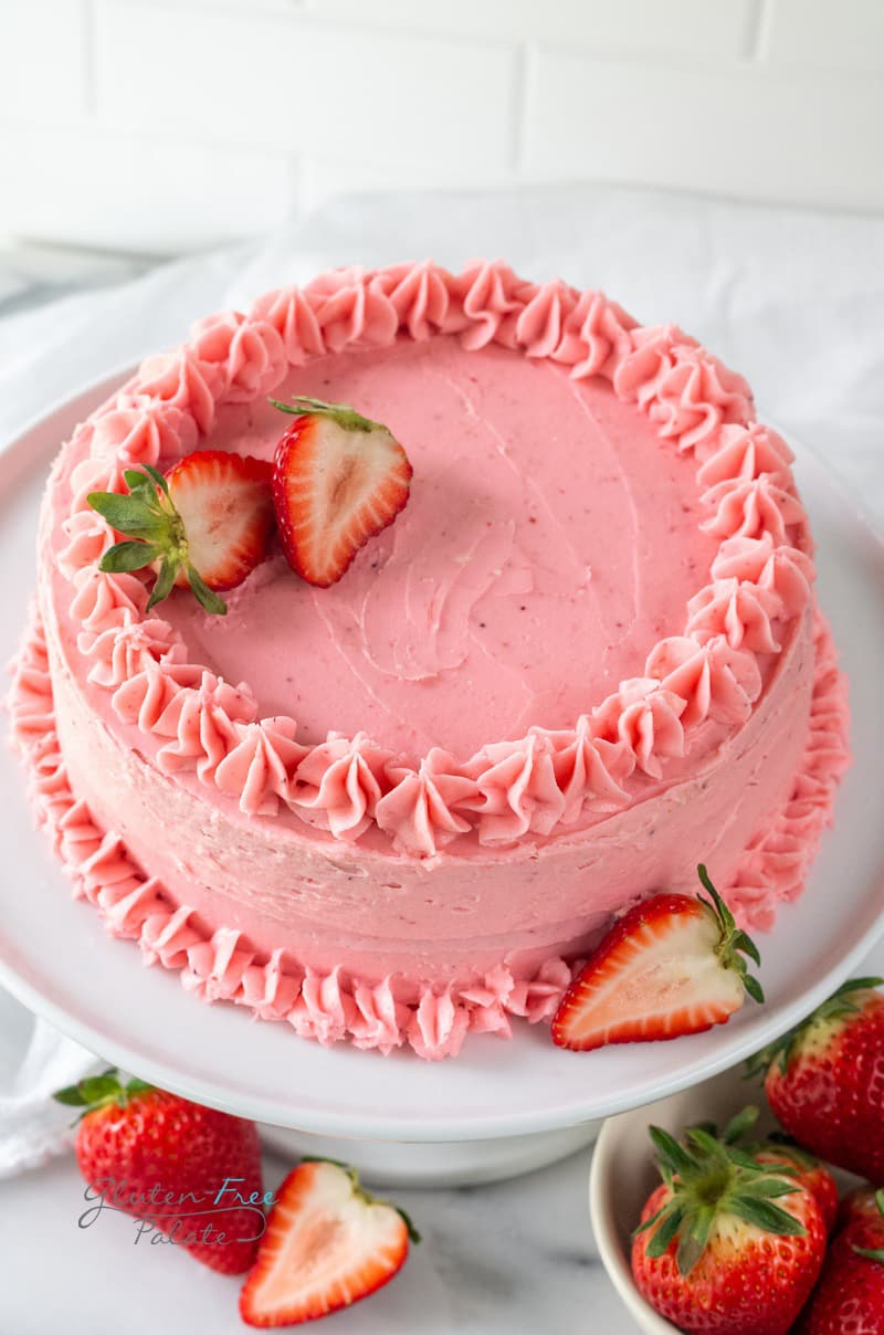 angled view of a gluten free strawberry cake on a white cake platter