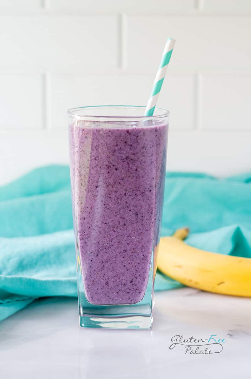 chia seed smoothie in a glass with a blue striped straw
