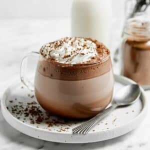 gluten free hot cocoa in a clear mug topped with whipped cream