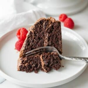 gluten free chocolate cake on a white plate with a fork taking a bite