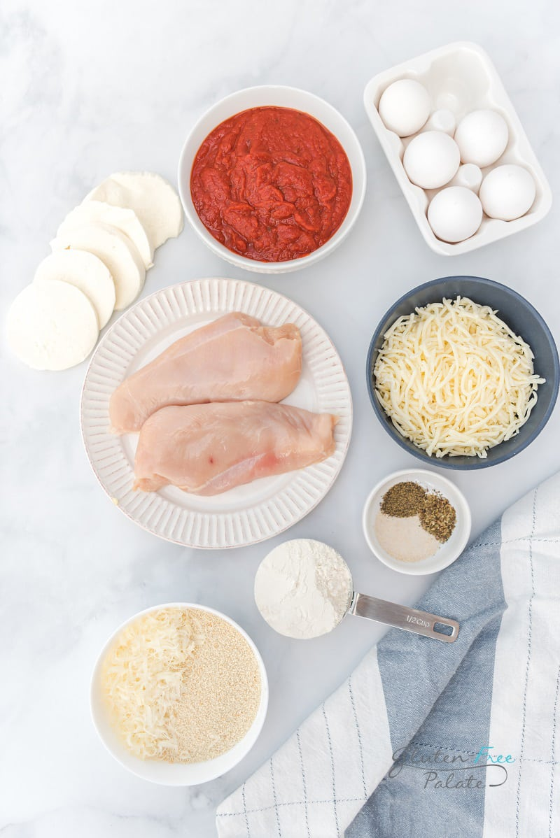 Top down view of the ingredients needed for gluten free chicken parmesan, including chicken, bread crumbs, cheese, sauce, eggs, and seasonings