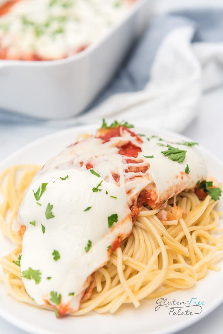 a plate of spaghetti topped with cheesy chicken parmesan.