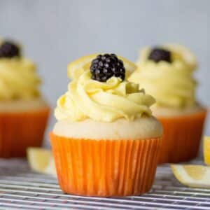 gluten free lemon cupcake topped with frosting and a blackberry