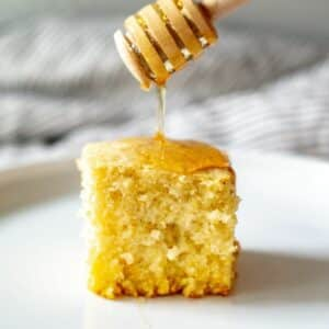 gluten free cornbread on a white plate with honey drizzled on top