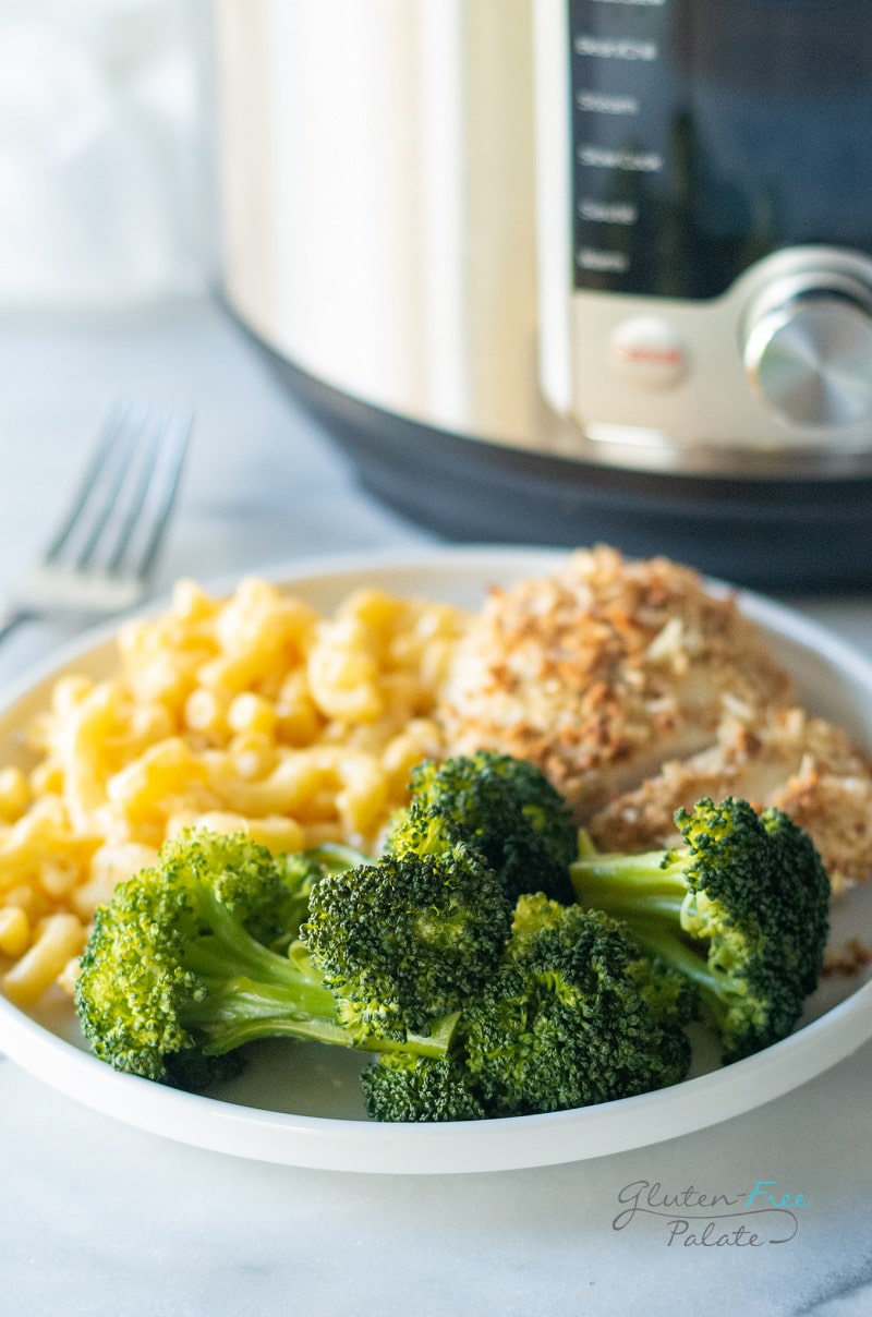 instant pot steamed broccoli on a plate with chicken and noodles