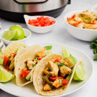 a plate of three soft chicken tacos filled with chicken and peppers, garnished with lime. The plate s in front of an instant pot.