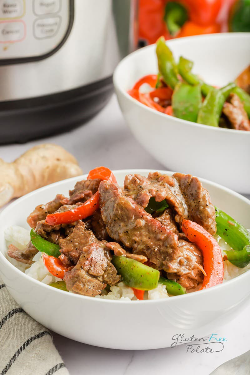 sliced steak with red and green peppers on top of a bowl of rice next to an instant pot