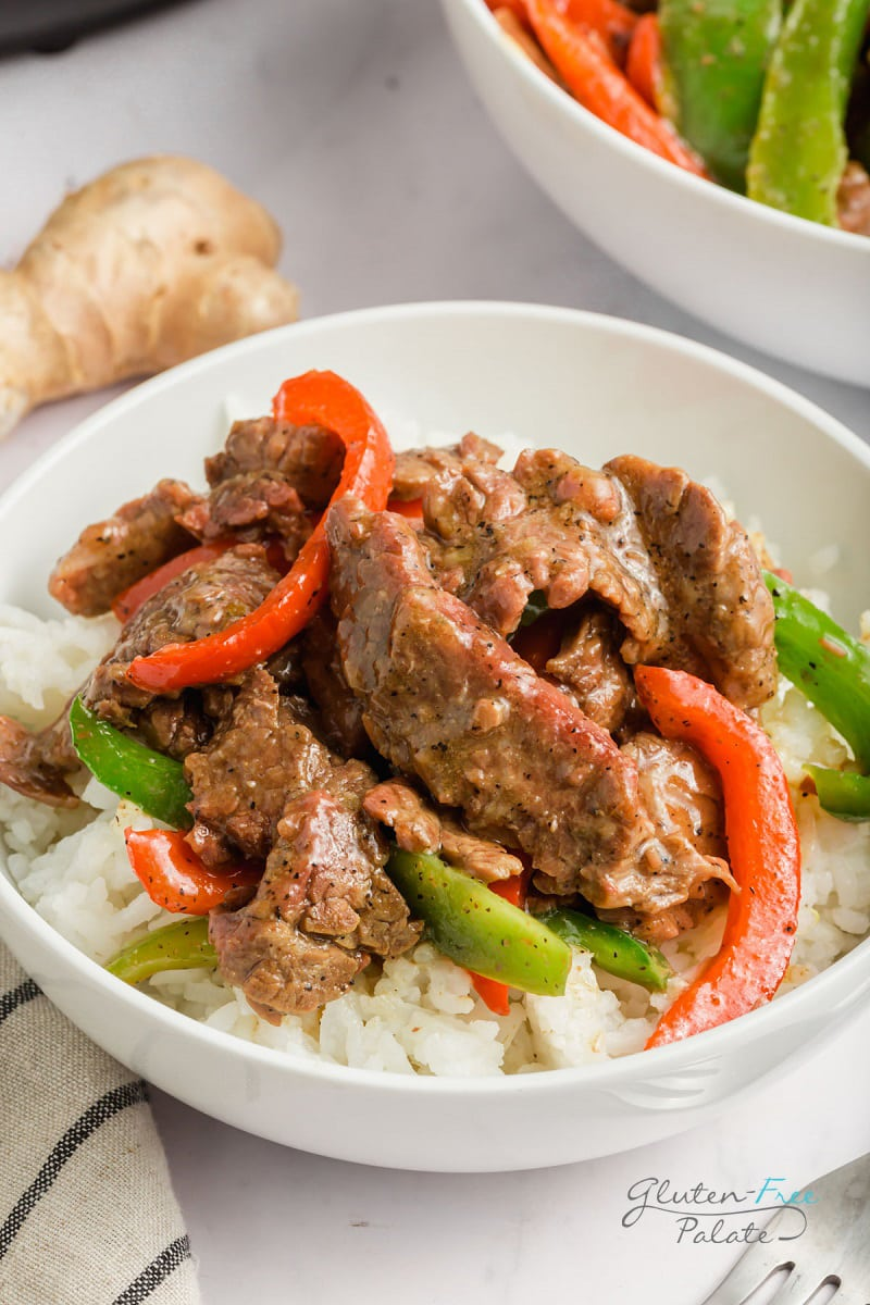 closeup view of pepper steak and rice in a white bowl on a counter
