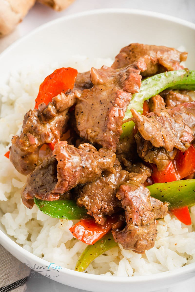 closeup view of sliced steak and peppers with rice.