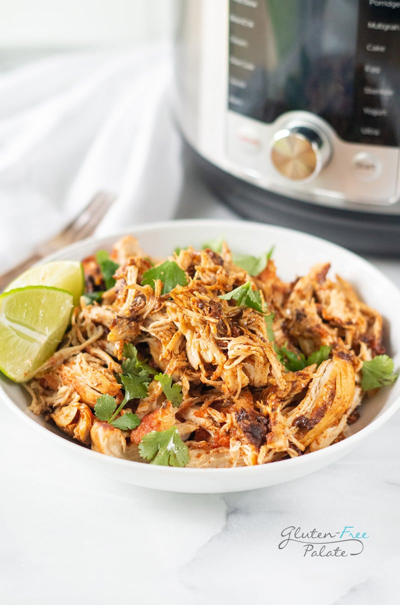 instant pot salsa chicken in a white bowl with a lime and garnish
