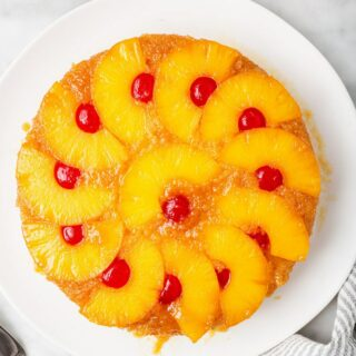 top down view of a round pineapple upside down cake topped with pineapple ring halves and cherries on a white plate.