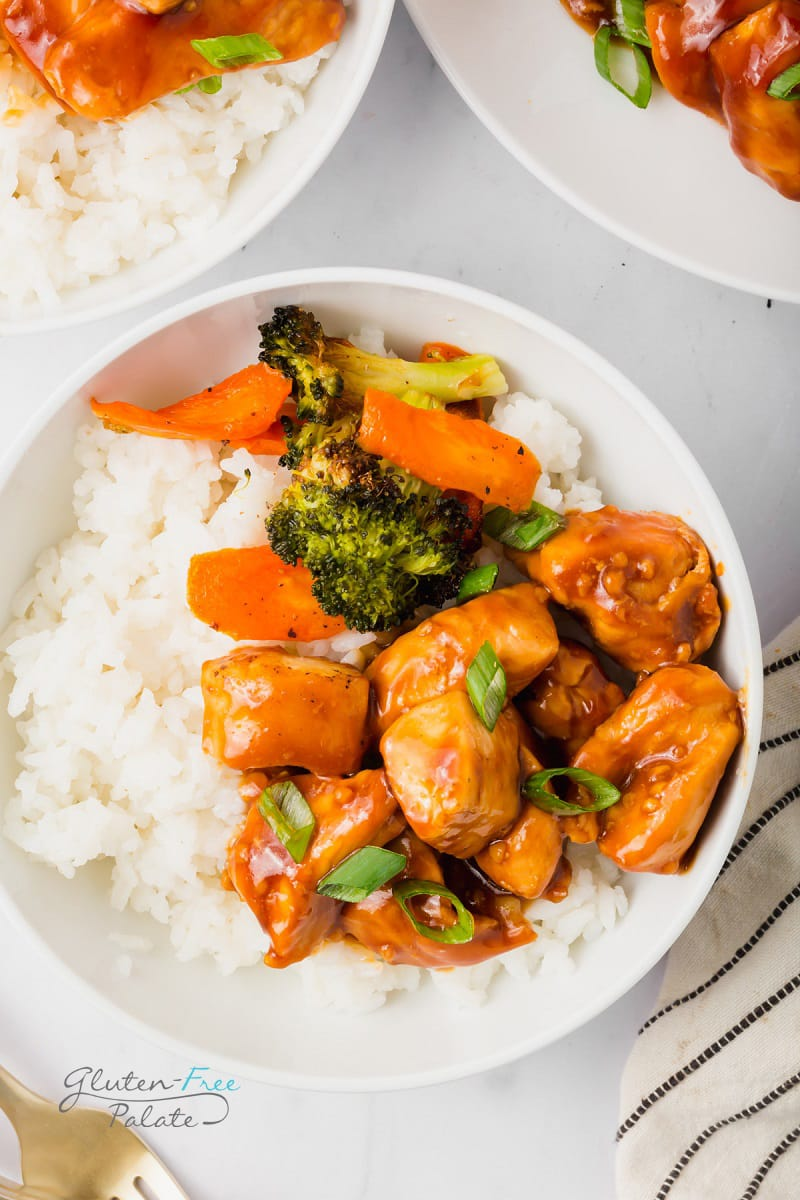 a bowl of white rice topped with teriyaki chicken, carrots, and broccoli