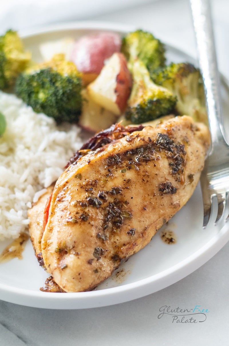 Stuffed chicken breast on a dinner plate with rice and roasted vegetables.