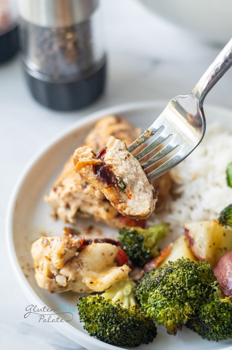 a dinner plate with rice, broccoli, potatoes and stuffed chicken breast. A bite of chicken is being lifted by a silver fork.