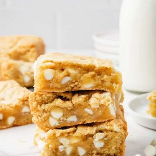 Three blondie bars filled with white chocolate chips and stacked on top of each other. In the background is a glass bottle of milk and more blondie squares.