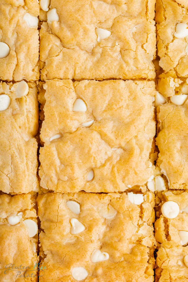 closeup view of a pan of blondies with white chocolate chips. The blondies have been sliced into squares, but not separated.