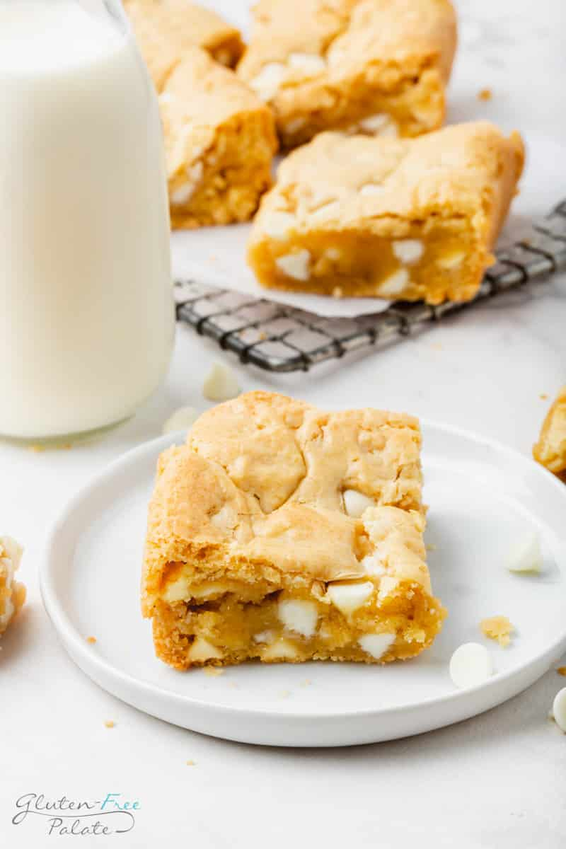 a corner piece of a blondie with white chocolate chips on a small white plate. In the background is a glass bottle of milk and more blondies on a metal baking rack.