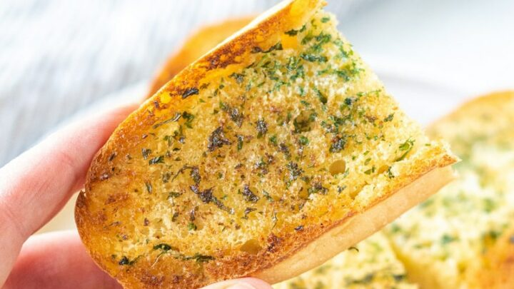 A hand holding an end piece of garlic bread over a plate filled with garlic bread.