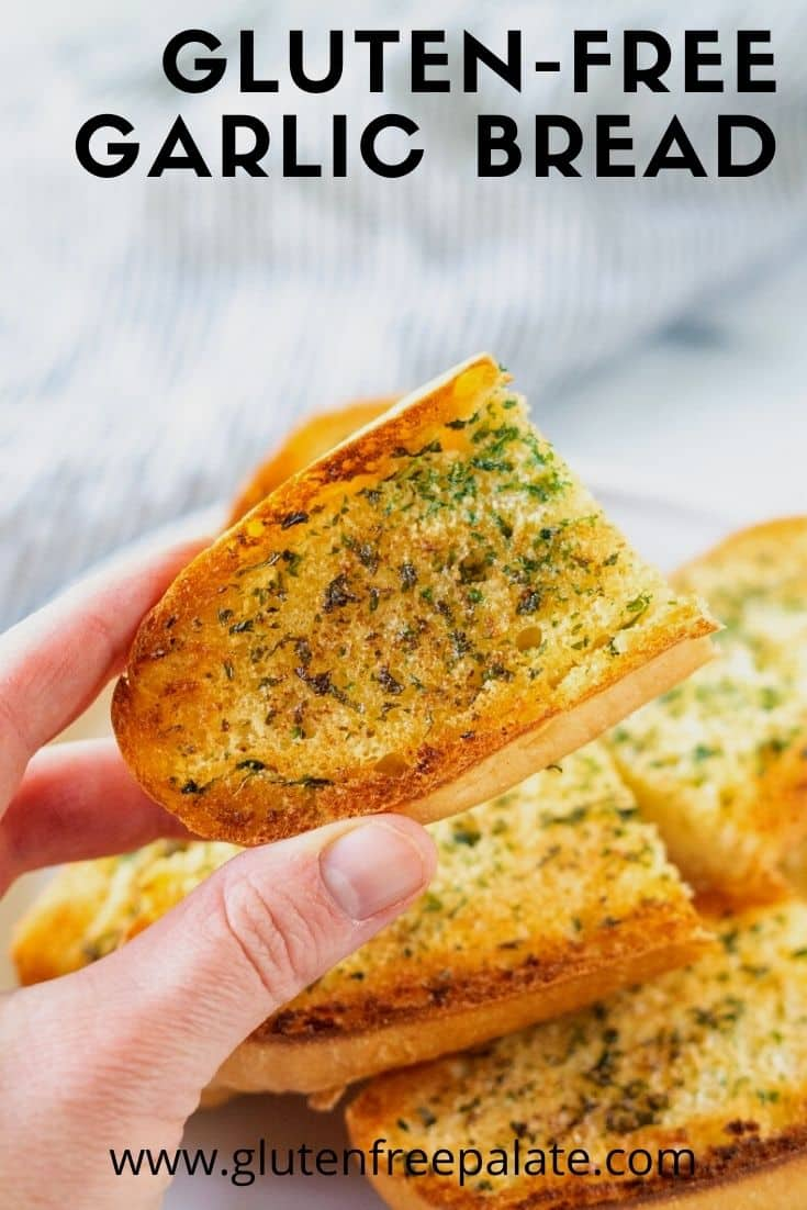A hand holding an end piece of garlic bread over a plate filled with garlic bread. Text overlay reads, Gluten free garlic bread.
