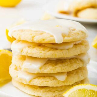 a stack of five glazed lemon cookies stacked on a white plate. A lemon wedge is in front of the plate, and another lemon wedge is behind the stack of cookies.