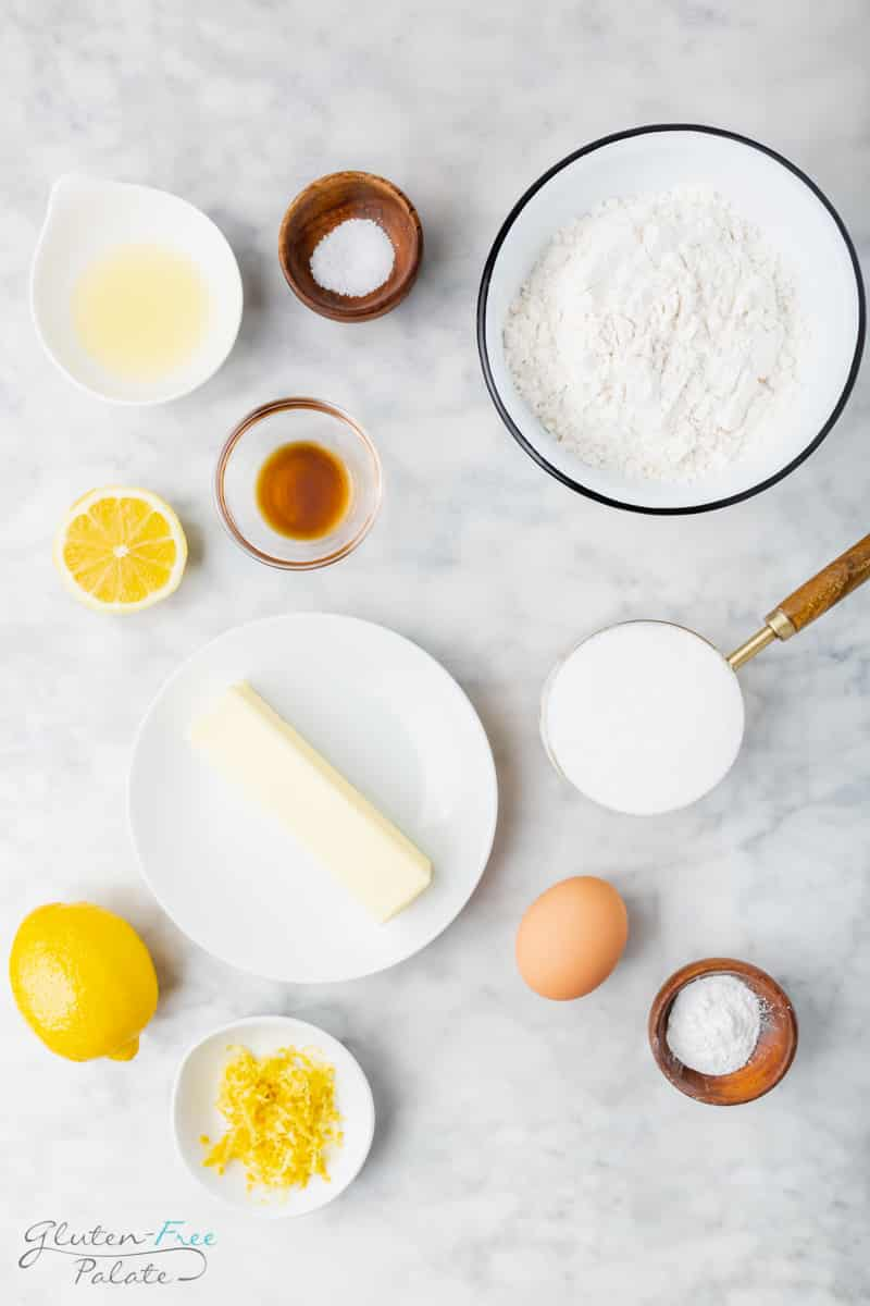Top down view of each of the ingredients needed to make gluten free lemon cookies in separate bowls. There is a bowl of flour, a plate with a stick of butter on it, a cup of sugar, an egg, lemon juice, lemon zest, salt, baking powder, and vanilla extract.
