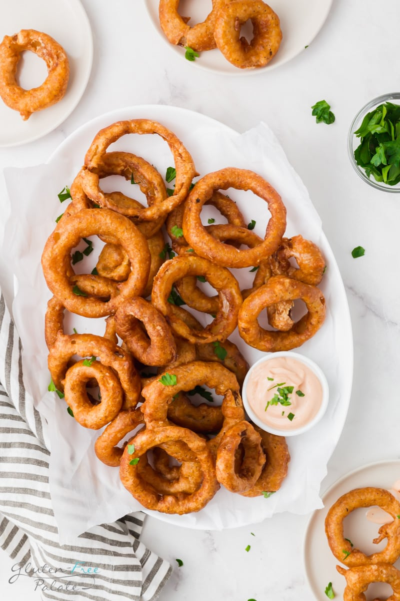 an oval platter of battered onion rings with a side of creamy dip.