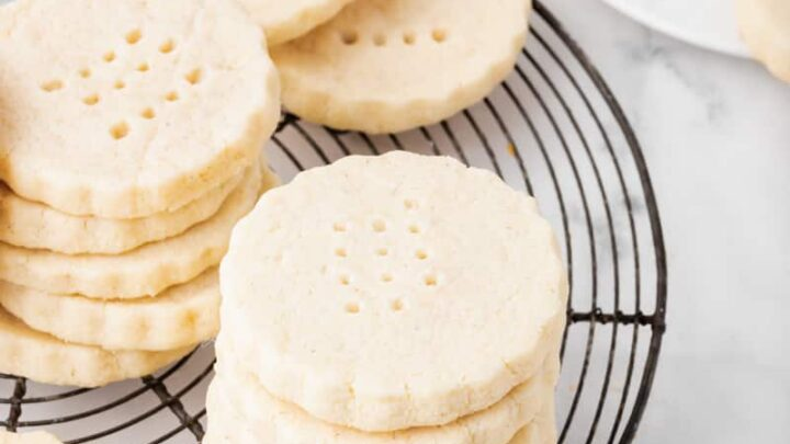 stacks of scalloped round shortbread cookies on a round, black cooling rack.