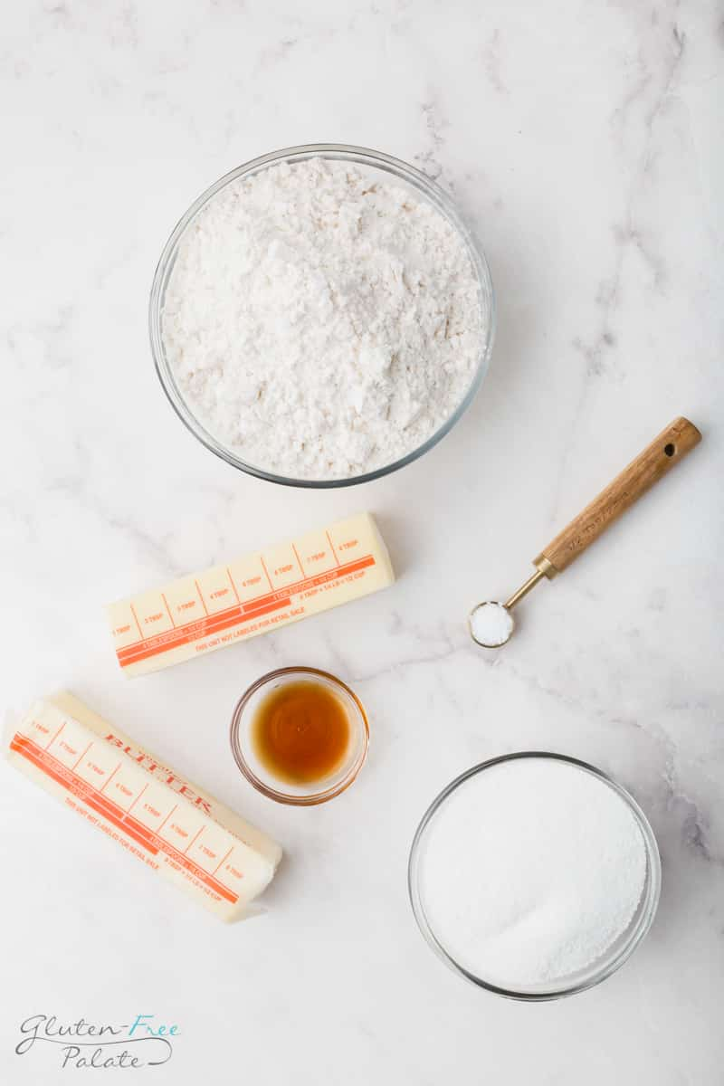 Ingredients for gluten free sugar cookies shown from the top down. Includes a bowl of flour, a bowl of sugar, a teaspoon of salt, a small bowl of vanilla, and a stick of butter