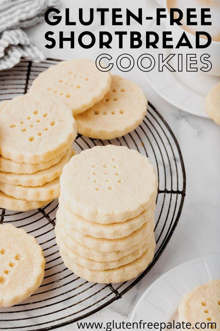 a round, black cooling rack topped with stacks of round shortbread cookies with scalloped edges.